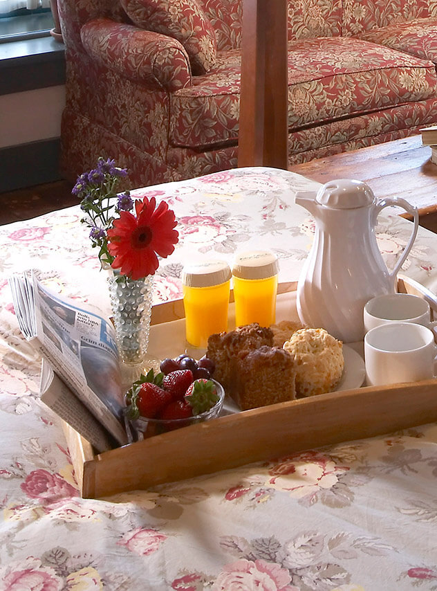 breakfast tray with muffins and fruit sitting on bed