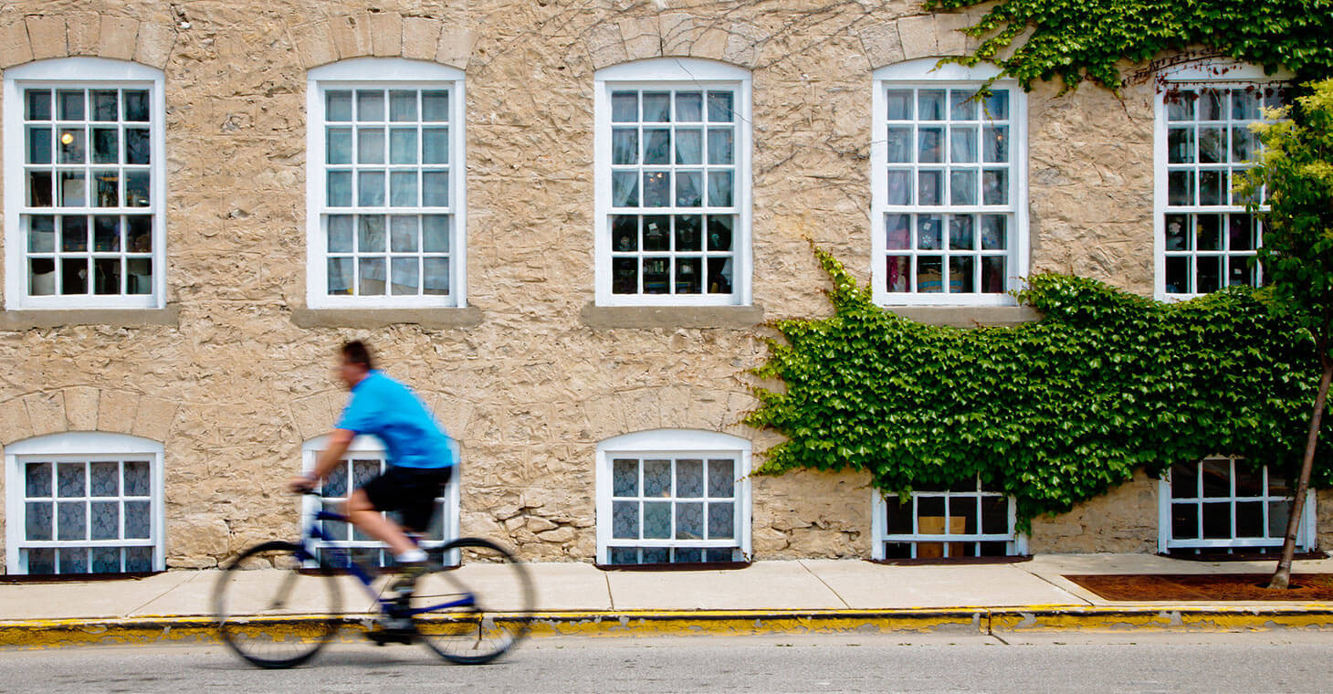 Man riding a bike in front of a building