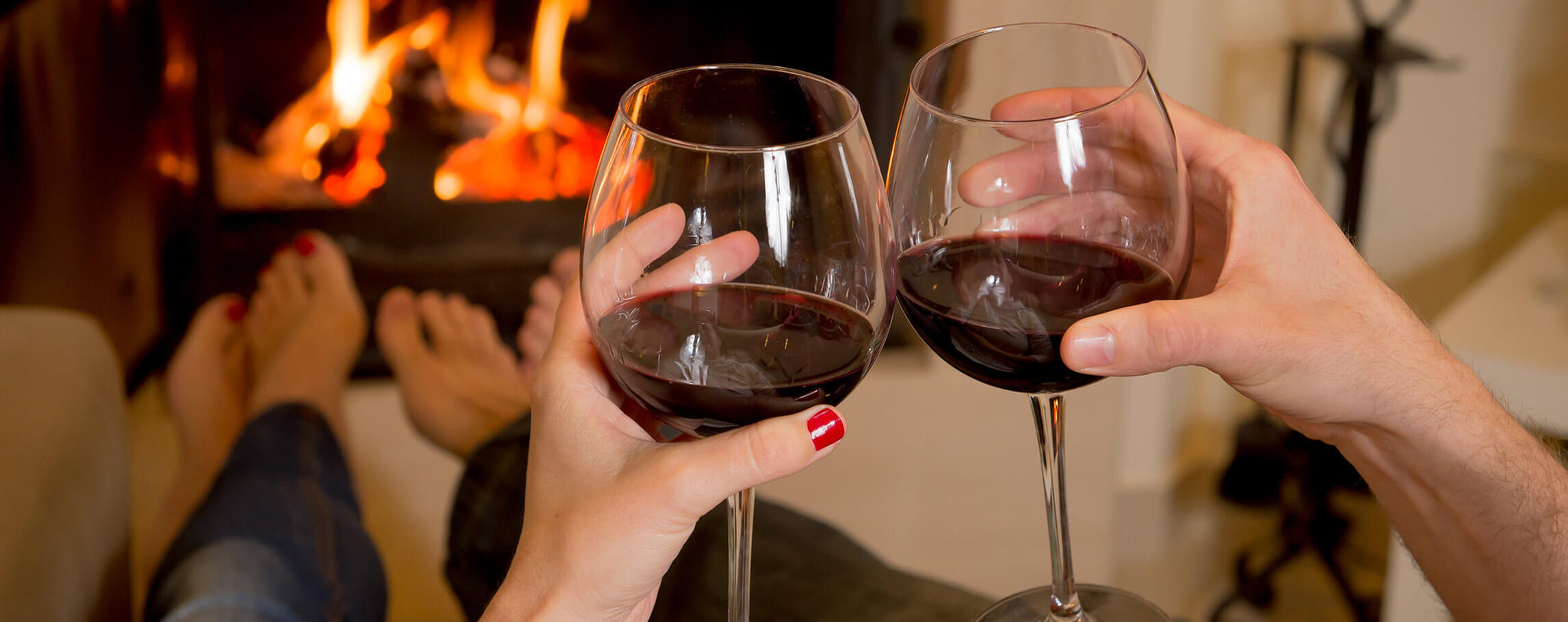 Couple drinking wine in front of a fire