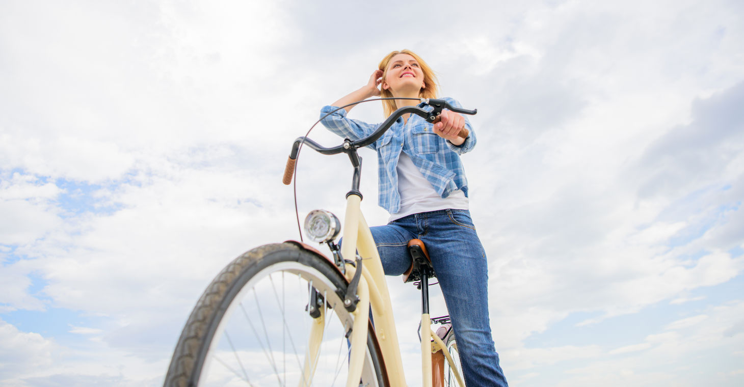Top Bike Trails in Cedarburg - A girl on a bike with clouds in the background