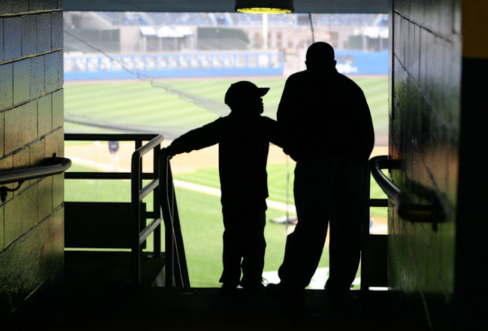 a father and son attend a baseball game