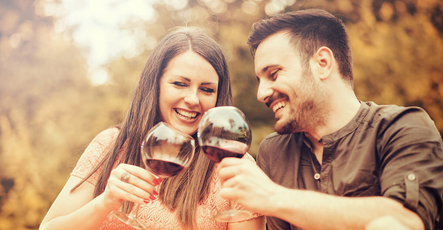 a man and woman laughing and drinking red wine