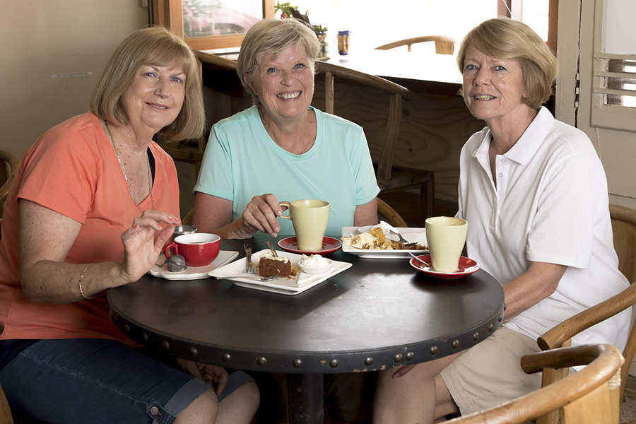 Three ladies having coffee and pastries at a cafe