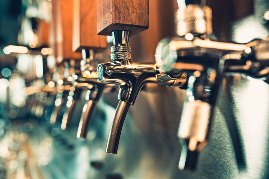 a row of beer taps at a bar