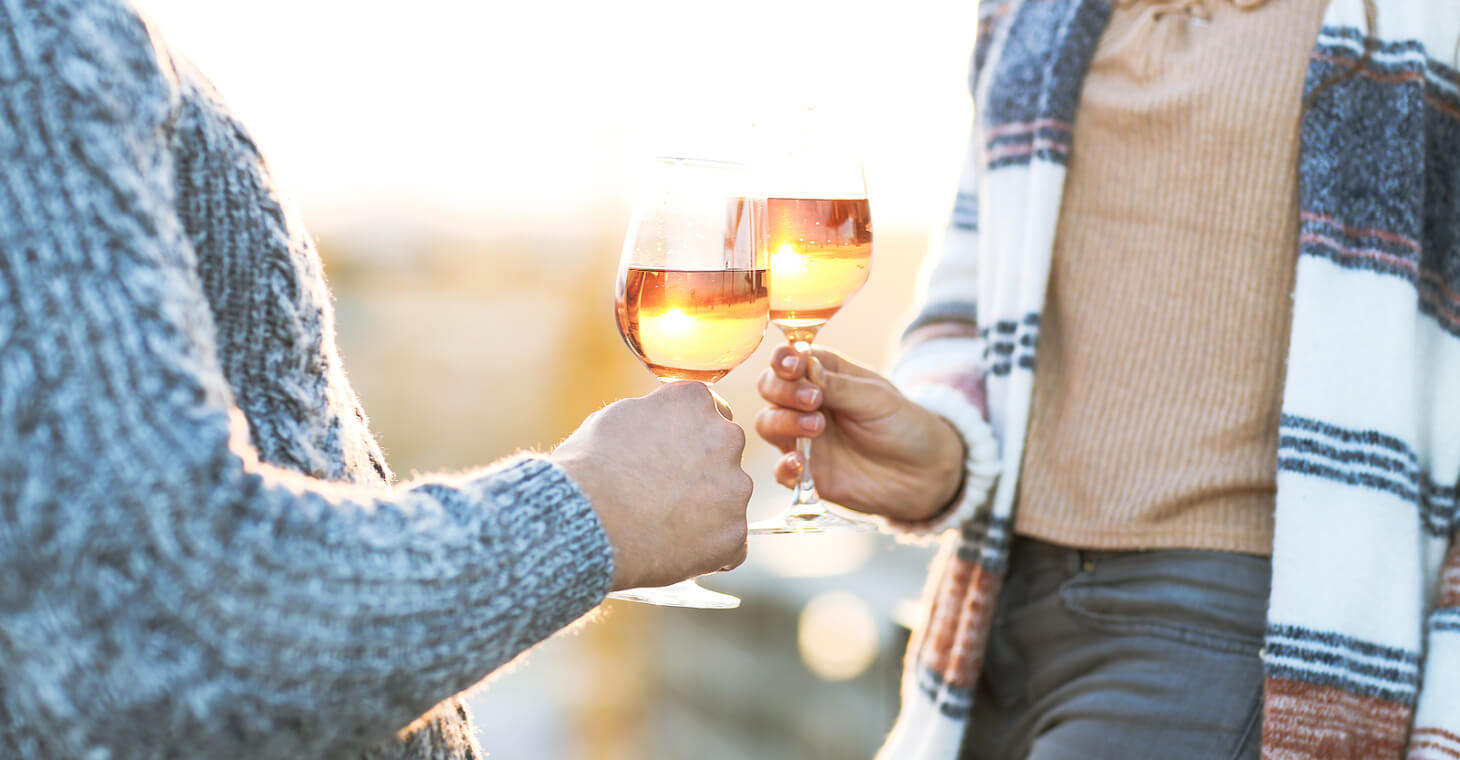 Two women holding a glass of rose wine outside