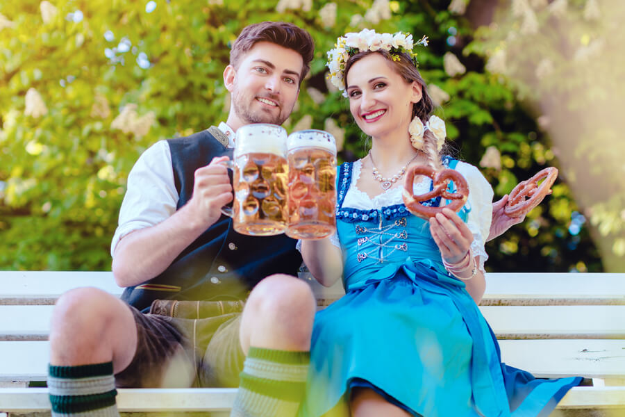 couple at Cedarburg Oktoberfest on a bench with beers